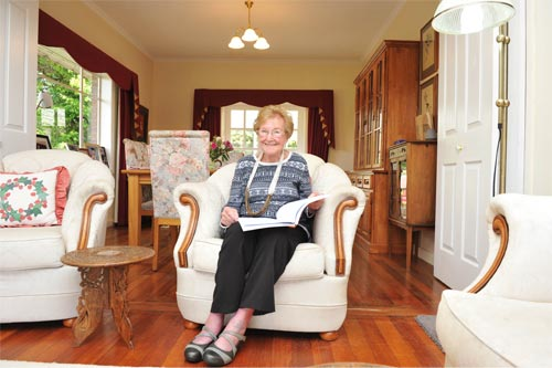 Joan sits in an armchair with a book on her lap at home