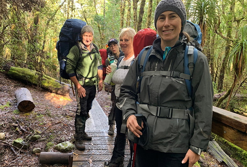 Photo of a woman with hikers in the background on a trail