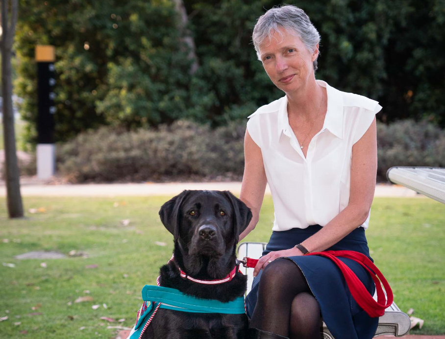 Elizabeth Barnes, CEO is seated with Bazza, our dog-assisted therapy dog.