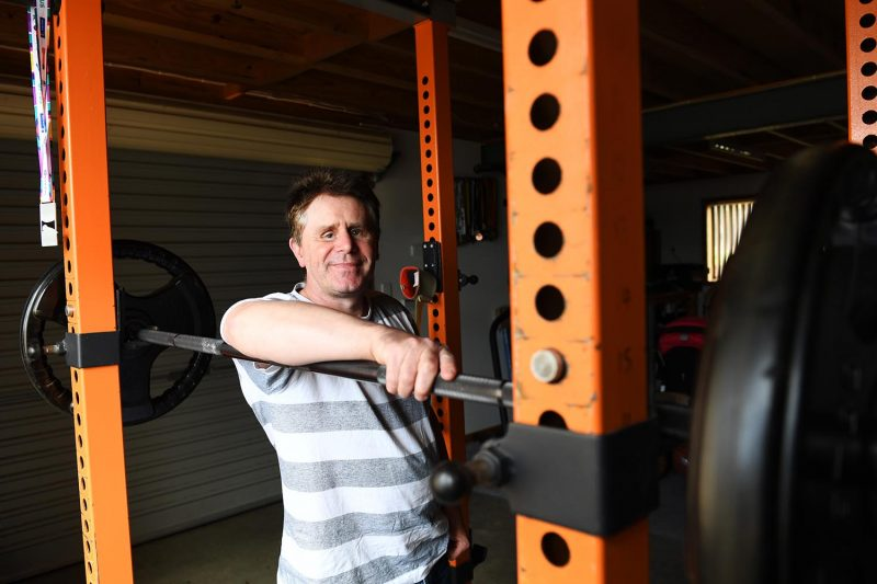 Image of a man leaning on a bench press with large weights and smiling at the camera