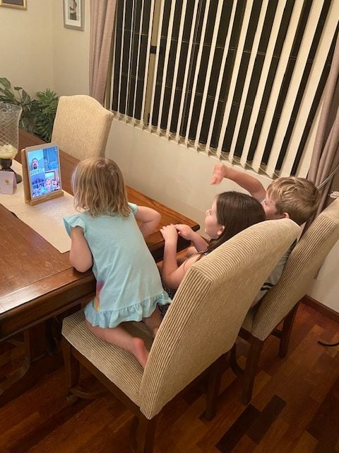 Group of three young children sit on sofa and look at screen in front of them
