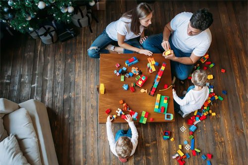 Aerial shot of two children and their parents playing with Lego on a wooden table.