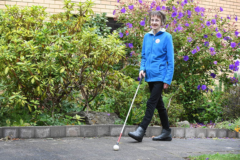 Suzanne walking in a garden with her mobility cane