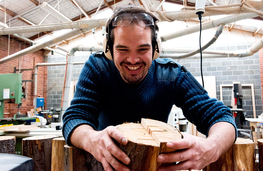 Duncan working with wood in his woodworking studio.