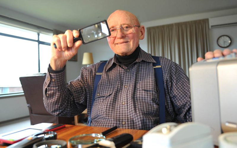 A man surrounded by assistive technology holds a magnifier.