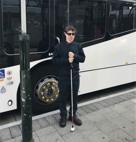 Man holding a mobility cane at a bus stop