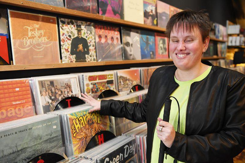 A woman flicks through record albums.