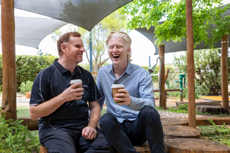 Two mean laugh while drinking coffee in a park