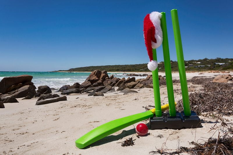 Beach cricket bat with a Santa hat hanging on the wickets