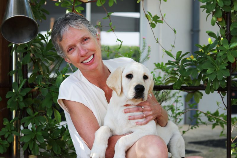 A woman holding a puppy smiling