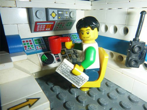 Lego scene with figure sat in a chair in front of a console with a cup, CB radio
