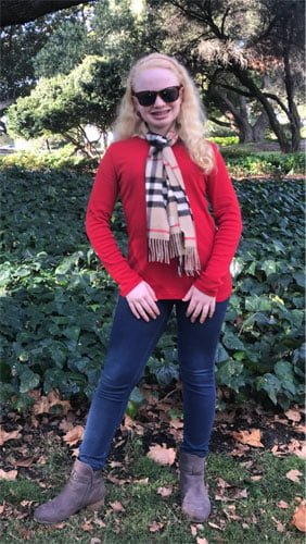 Karin standing in a lush green garden, wearing a red top, a scarf, and blue jeans.