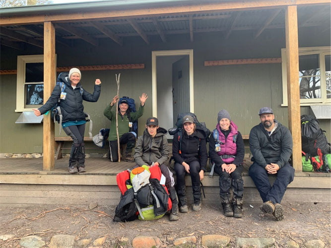 Group of hikers facing the camera and smiling, while sitting on the veranda of a hiking hut with backpacks.