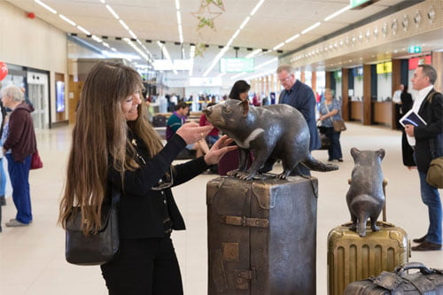 Artist Ruth Watherhouse checks out the Braille under the chin of the tasmanian devil sculpture at the airport.