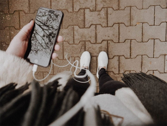 A birds eye view image of a person holding a phone with headphones plugged in.