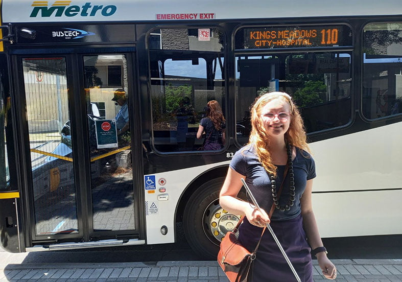 A young woman standing at a bus stop with a bus behind her